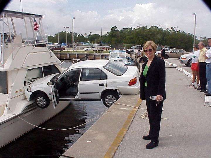 Coche caído entre el espigon de un puerto y un yate, mujer en primer plano