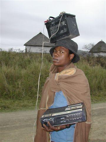 Persona con batería de coche sobre la cabeza, conectada a una radio