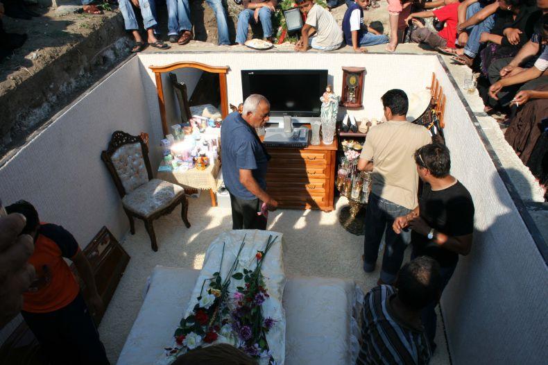 Personas colocando los objetos en la tumba